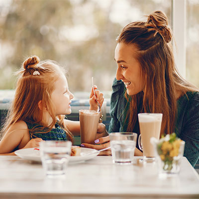 Mother and daughter having milkshakes at a cafe